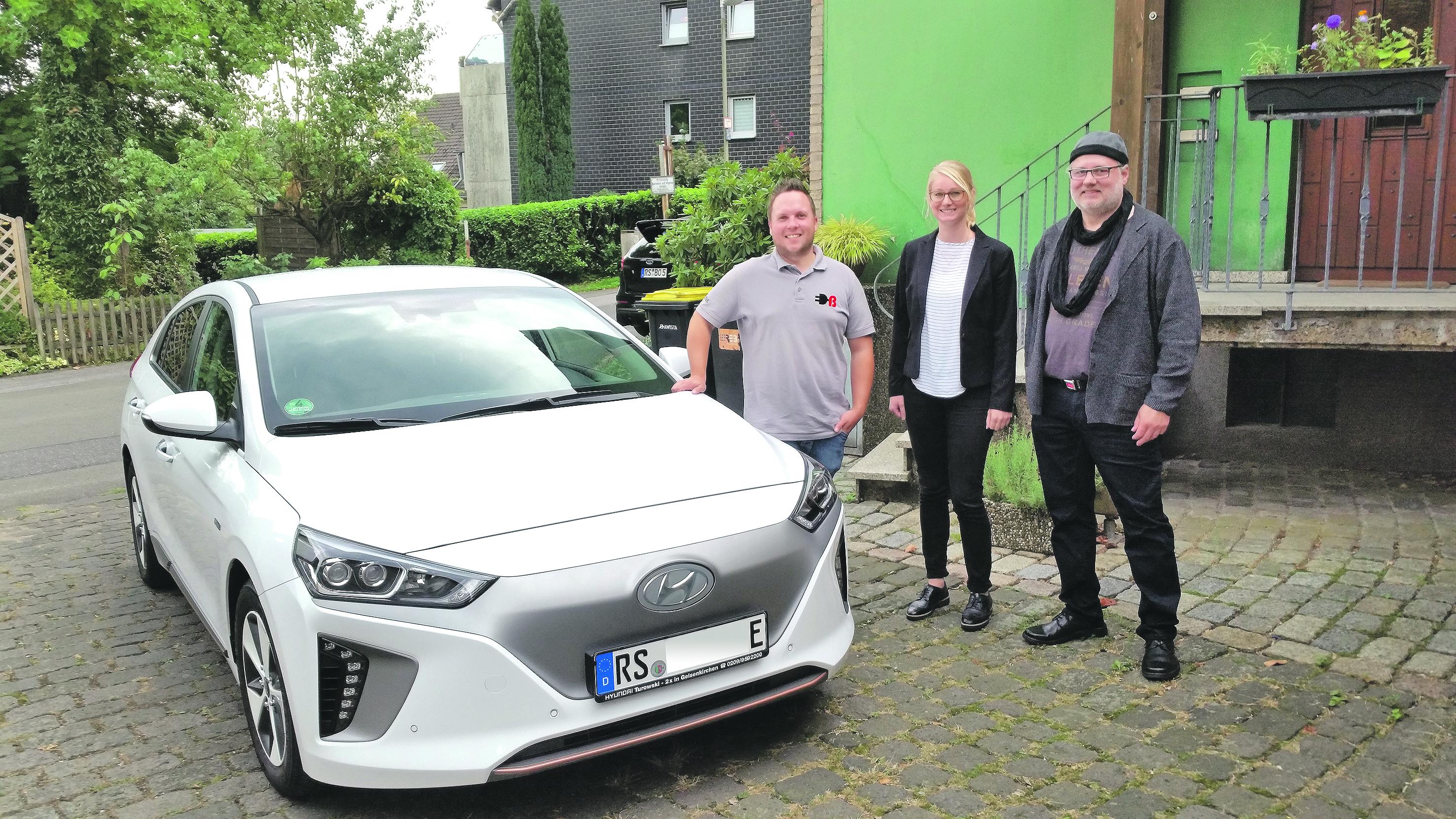 Kevin Bornewasser (emobitec), Maren Koppelberg (EWR) und der erste Besitzer einer EWR-Wallbox zum Laden von E-Autos in der heimischen Garage Stefan Zwanzig-Müller vor einem reinen E-Automobil. Foto: Sascha von Gerishem
