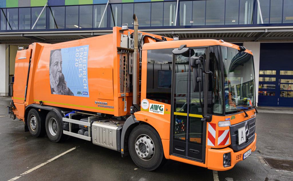 Die Müllwagen der Abfallwirtschaftsgesellschaft mbH Wuppertal (AWG) fahren mit Engels-Plakaten durch die Stadt. Foto: obs/WSW Wuppertaler Stadtwerke GmbH/Stefan Tesche-Hasenbach