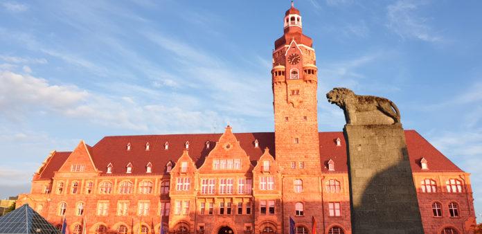 Als weithin sichtbares Zeichen gegen häusliche Gewalt wird das Remscheider Rathaus am 25. November, dem Internationalen Gedenktag für Opfer von Gewalt an Frauen und Mädchen, orange angestrahlt. Artwork: Sascha von Gerishem