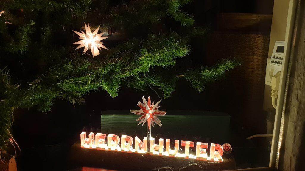 Das Schild im Schaufenster vom Flair-Weltladen in Remscheid-Lüttringhausen zeigt es an: Hier gibt es Herrnhuter Sterne. Foto: Sascha von Gerishem