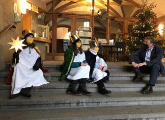 Ann-Sophie Kurp, Pia und Kim Kuhstoß mit OB Burkhard Mast-Weisz im Rathauseingang. Zu sehen ist im Hintergrund noch der Segenswunsch aus dem vergangenen Jahr. Der wird nun erneuert. Foto: Viola Juric