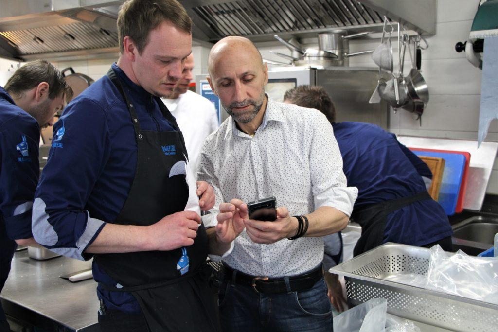"""Mitte April 2020. Endlich kommt wieder etwas Leben in die Restaurant-Küche des """"Blauer Esel"""" in Rostock. Miro B. bespricht mit seinem Küchenchef, wie das Ostermenü to-go zusammengestellt werden kann. Die Abholgerichte können den Umsatzausfall zwar nicht ausgleichen, aber es tut gut, dass wieder etwas passiert. Das Restaurant hat sich sogar eine eigene Abhol-App von einem Gast entwickeln lassen. ©ZDF/Enrico Demurray"""