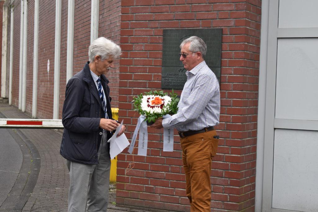 Hans Heinz Schumacher, 1. Vorsitzender der Gedenk- und Bildungsstätte Pferdestall, übergibt Blumen an Peter Auwerda. Foto: Peter Klohs