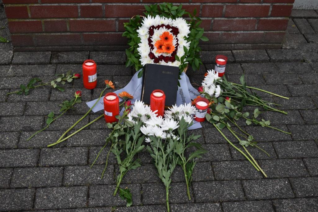 Die alte Bibel mit Blumen und Kerzen unter der Gedenktafel. Foto: Peter Klohs