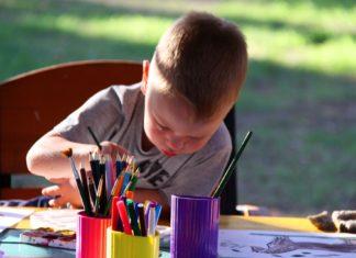 Ein kleiner Junge malt ein Bild.