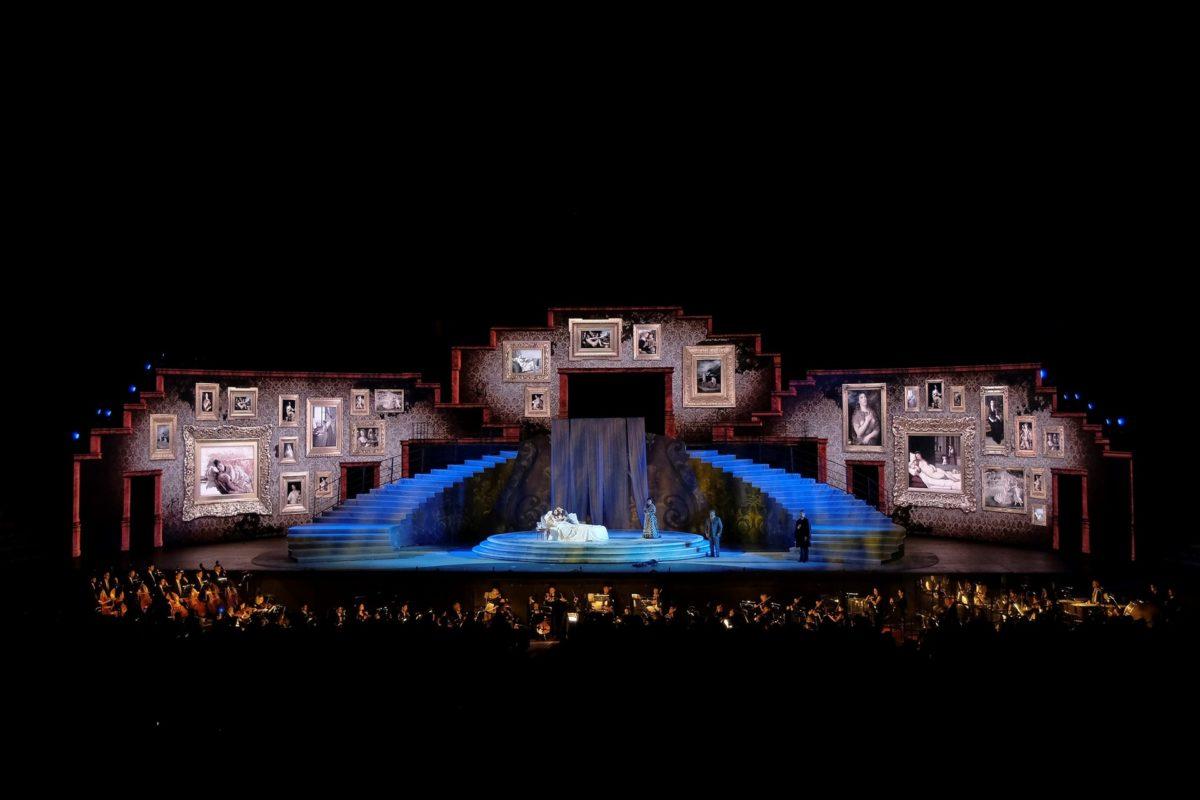 """""""Aus der Arena di Verona: Giuseppe Verdi - La Traviata"""": Eine riesige bunt ausgeleuchtete Bühne mit Orchester in der dunklen Arena. © ZDF / EnneviFoto"""