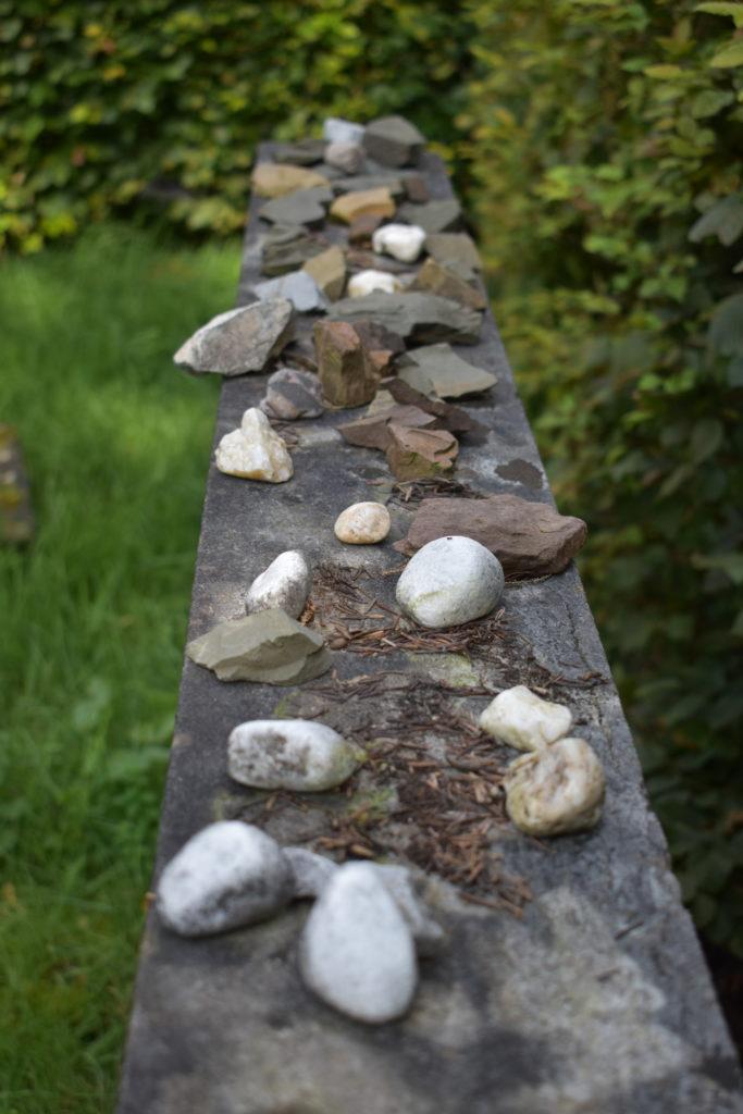 Der verwitterte Grabstein in der Grabstätte der Familie Löwenthal, nach jüdischem Brauch mit Steinen zum Zeichen der Erinnerung und Trauer bedeckt. Foto: Peter Klohs